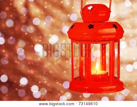 Red antique Christmas lantern with burning candle inside hanging on bokeh blur background, traditional Christmastime decoration
