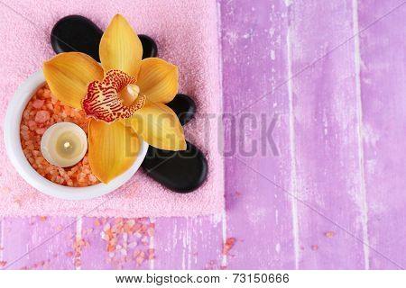 Still life with beautiful blooming orchid flower, towel and sea salt in bowl on color wooden background