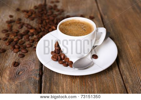 Cup of coffee with milk and coffee beans on wooden background
