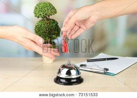 Female hand giving hotel key on reception desk, on bright background