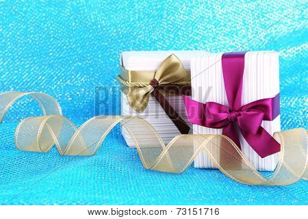 Holiday gift boxes decorated with vinous and golden ribbons on blue fabric background