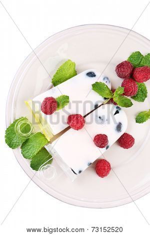 Tasty ice cream pops with fresh berries on plate, isolated on white