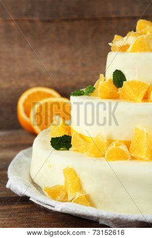 Beautiful wedding cake with oranges on  wooden background