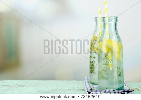 Tasty cool beverage with lemon and thyme, on light background