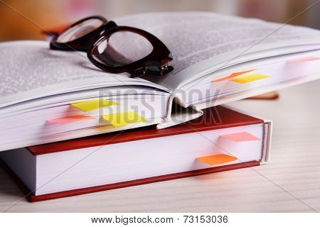 Books with bookmarks and glasses on table on bright background