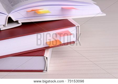 Books with bookmarks on wooden table