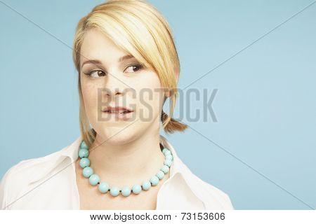 Studio shot of young woman biting lip