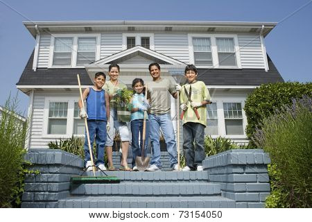 Hispanic family with gardening tools in front of house