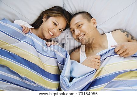 High angle view of Asian couple in bed