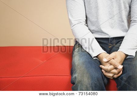 Man on sofa with hands clasped