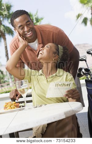 African couple smiling at each other at restaurant