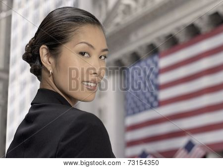 Asian businesswoman in front of American flag