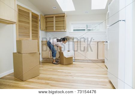 Asian woman unpacking boxes in new house