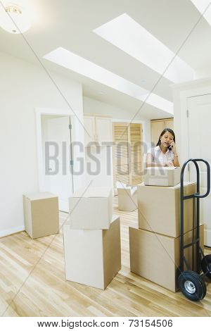 Asian woman talking on cell phone in new house