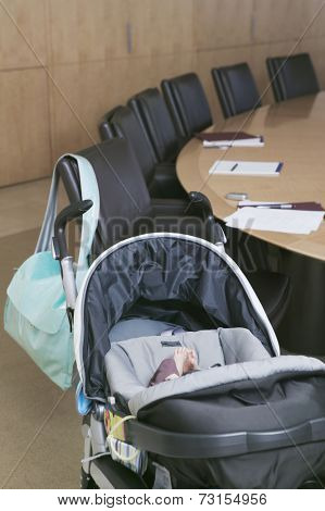 Baby in stroller next to conference table