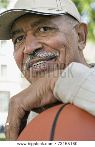 Close up of senior African man smiling with basketball
