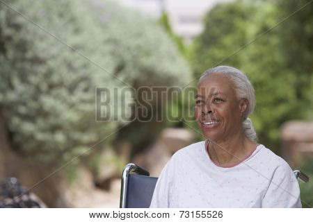 Senior African woman in hospital gown and wheelchair outdoors