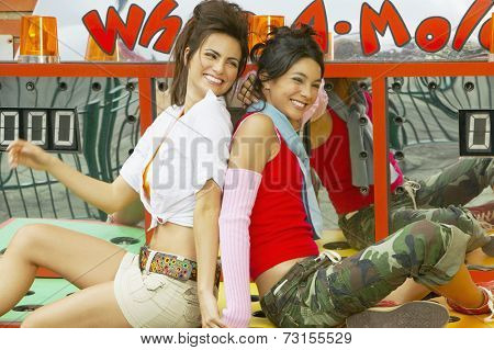 Two young Hispanic women sitting on carnival booth