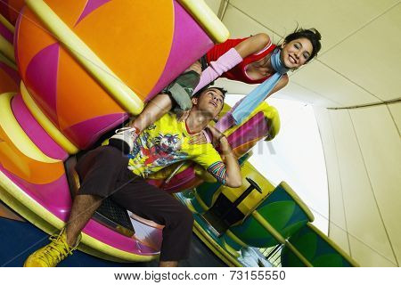 Teenage Hispanic couple sitting in teacup carnival ride