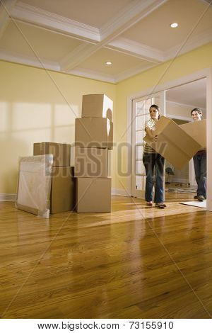 Hispanic couple carrying moving boxes