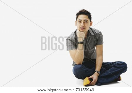 Portrait of Pacific Islander man sitting cross-legged
