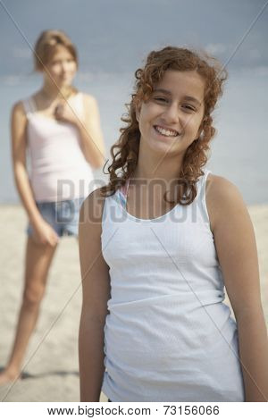 Teenage girl smiling on beach with friend in background