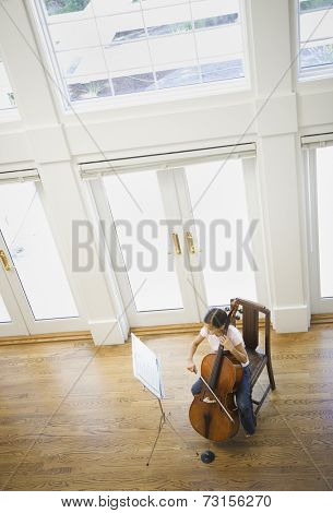 High angle view of Asian girl playing cello
