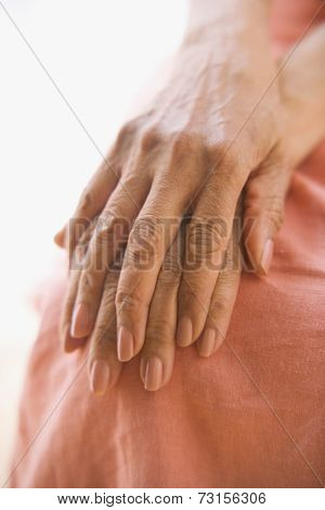 Close up of senior woman's hands on knee