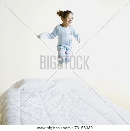 African girl jumping on bed