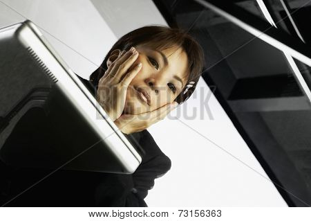 Low angle view through glass desk of Asian businesswoman and laptop