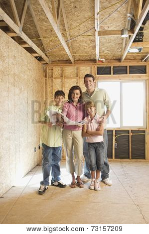 Family with blueprints on construction site