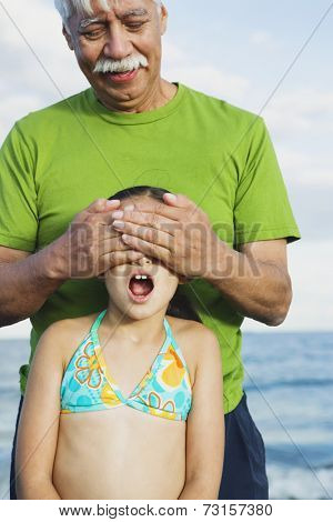 Hispanic grandfather covering granddaughter's eyes
