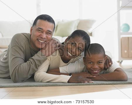 African family laying on livingroom rug smiling