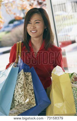 Asian woman carrying shopping bags