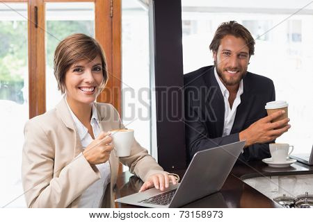 Business people smiling at the camera at the coffee shop