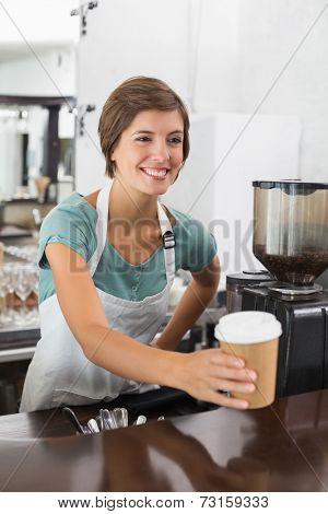 Pretty barista holding disposable cup at the coffee shop