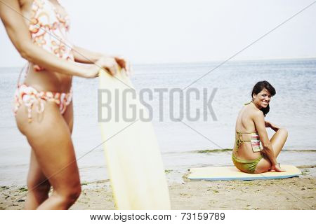 Young women with boogie boards at beach