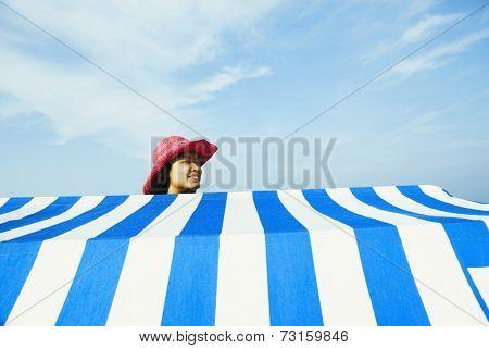 Hispanic woman standing behind beach sun shade