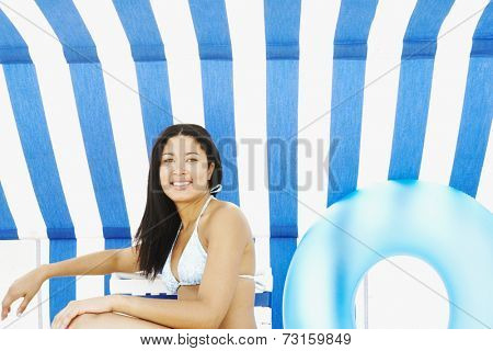 Hispanic woman sitting under beach sun shade
