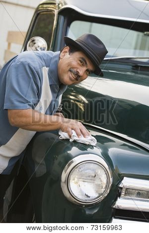 Middle-aged Hispanic man waxing classic car