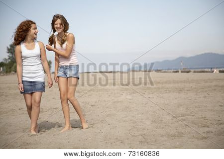 Two teenage girls walking on beach