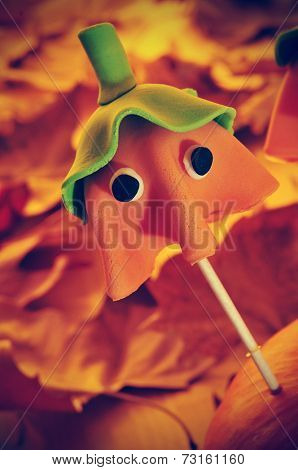 closeup of a homemade cake pop with the shape of a ghost Halloween pumpkin, with a retro effect