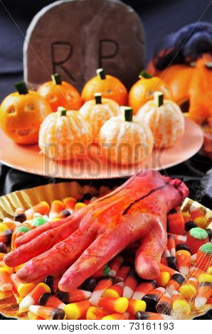some plates with different Halloween food, such as candies, mandarines as pumpkins, and scary ornaments such as an amputated hand or a grave