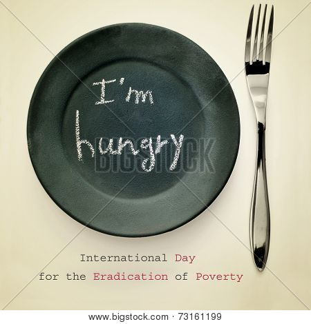 a fork and a plate painted as a chalkboard with the text I am hungry written in it, for the International Day for the Eradication of Poverty