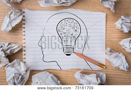 White note book paper with  pencil draw  light bulb inside a head and crumpled paper  on a wooden desk