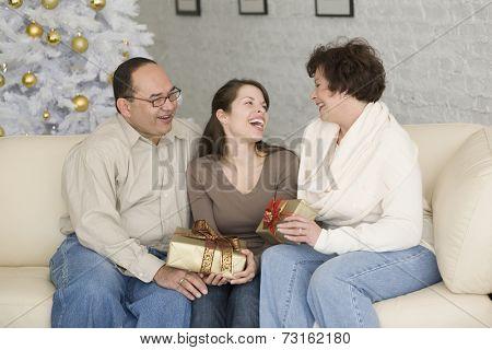 Hispanic family exchanging gifts on Christmas