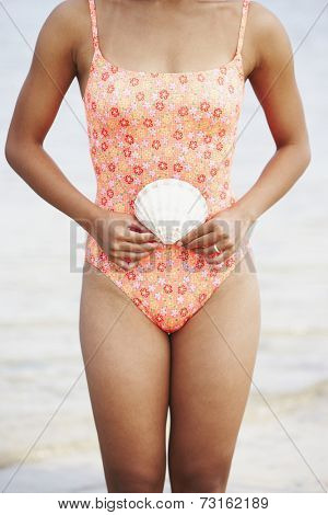 Woman in bathing suit holding seashell