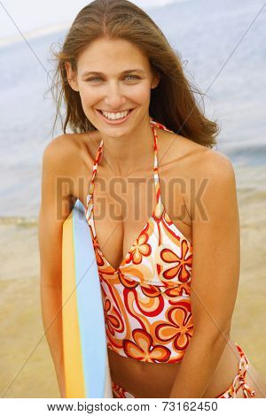 Young woman holding boogie board
