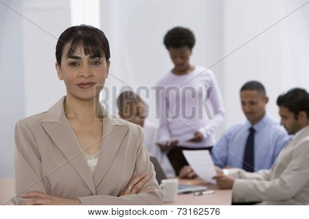 Indian businesswoman with co-workers in background