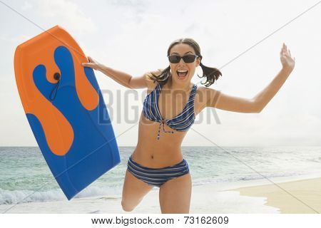 Woman running on beach with boogie board